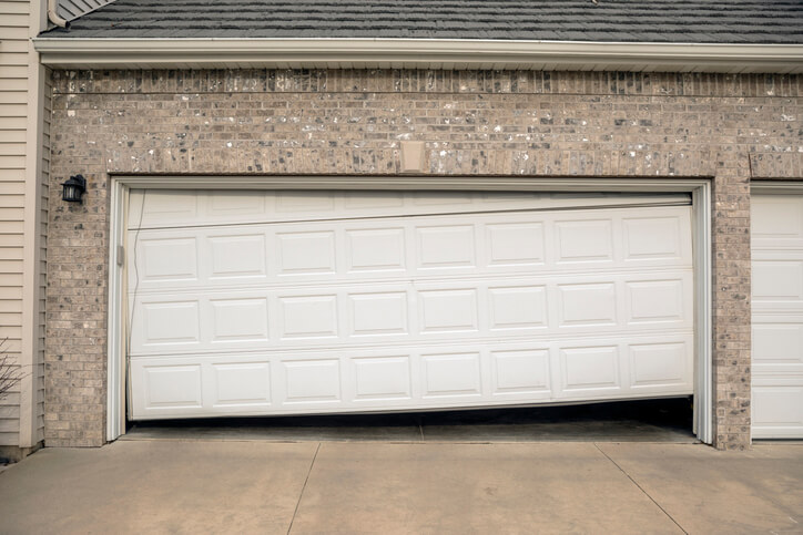 a garage door damaged and slanted
